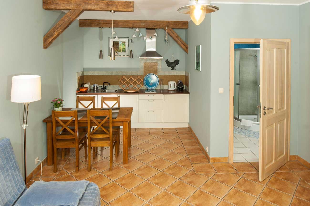 Tani apartament Muszelka widok na aneks kuchenny i łazienkę.