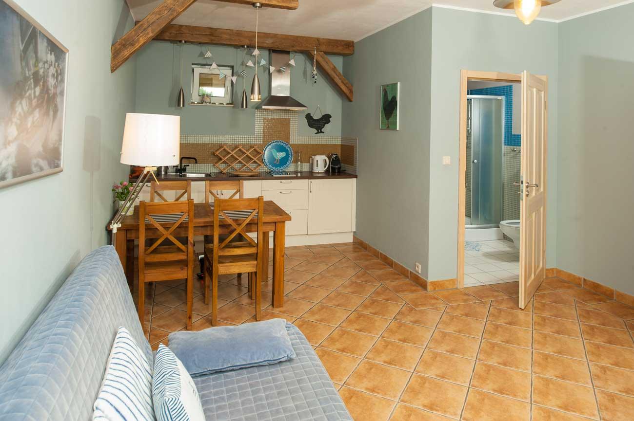 Widok na aneks kuchenny i łazienkę w Apartamencie Muszelka , nad morzem