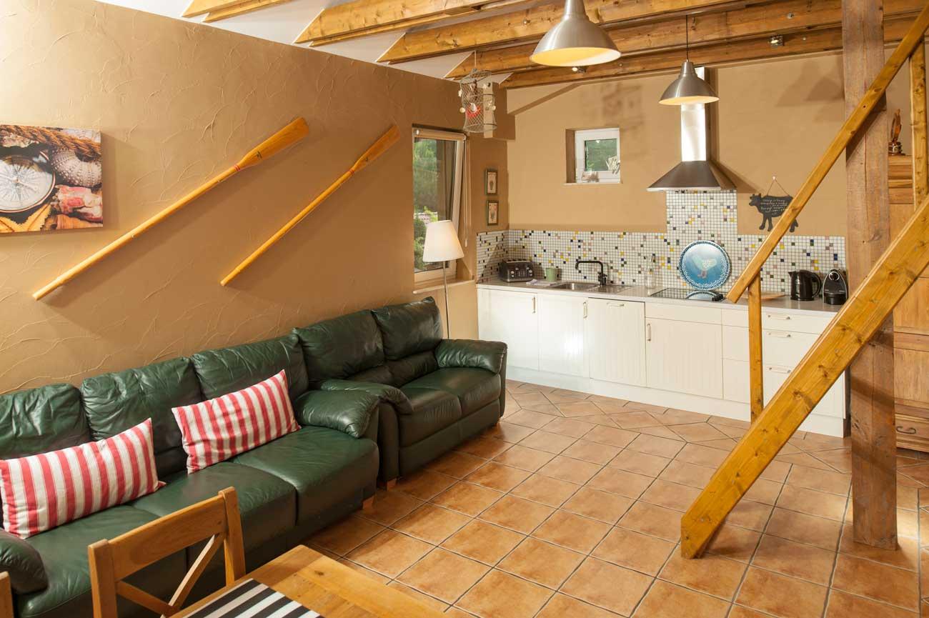 Tani apartament Róża Wiatrów widok na aneks kuchenny oraz sofy