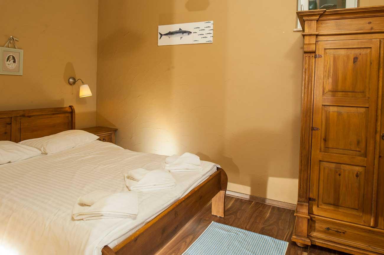 Widok na łóżko w sypialni Tani apartament Róża Wiatrów , nad morzem